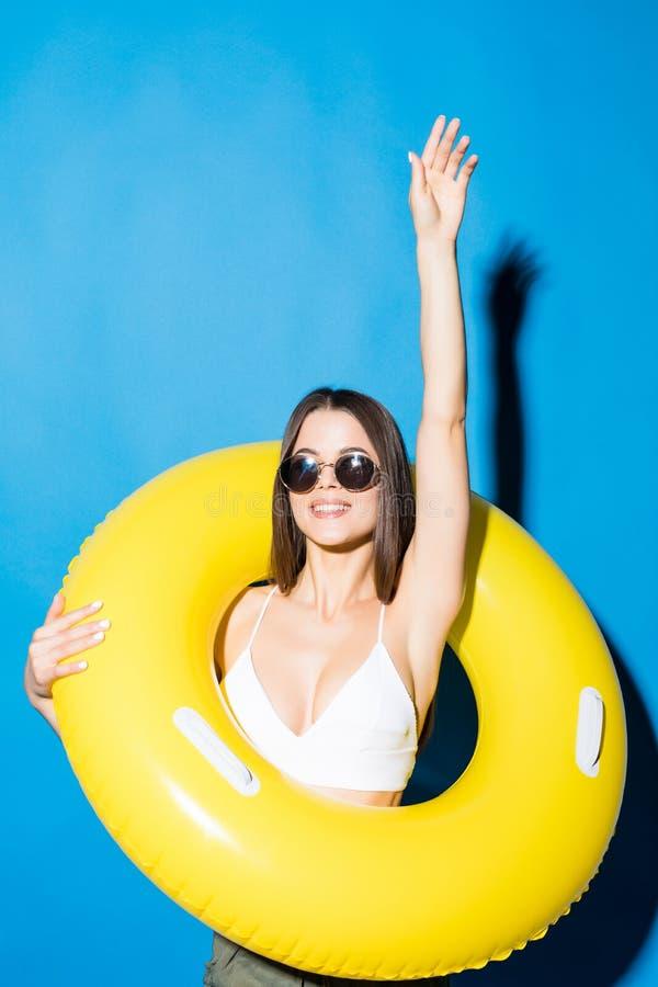 Retrato de una mujer de risa vestida en el traje de baño que mira a través del anillo inflable sobre fondo azul fotos de archivo