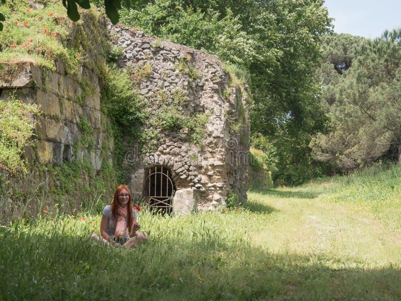Retrato de una mujer roja del pelo en hierba verde en Pompeya, Italia - mediodía caliente del verano foto de archivo libre de regalías