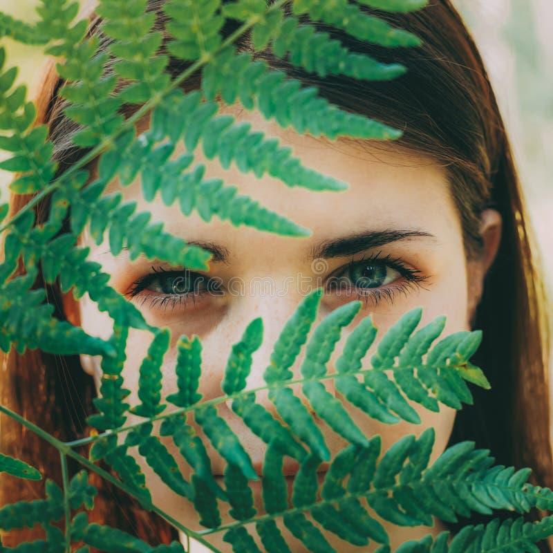 Retrato de una mujer roja de la muchacha del pelo de la belleza feliz joven que detiene a Fern Leaf Up To Face en bosque del parq foto de archivo libre de regalías