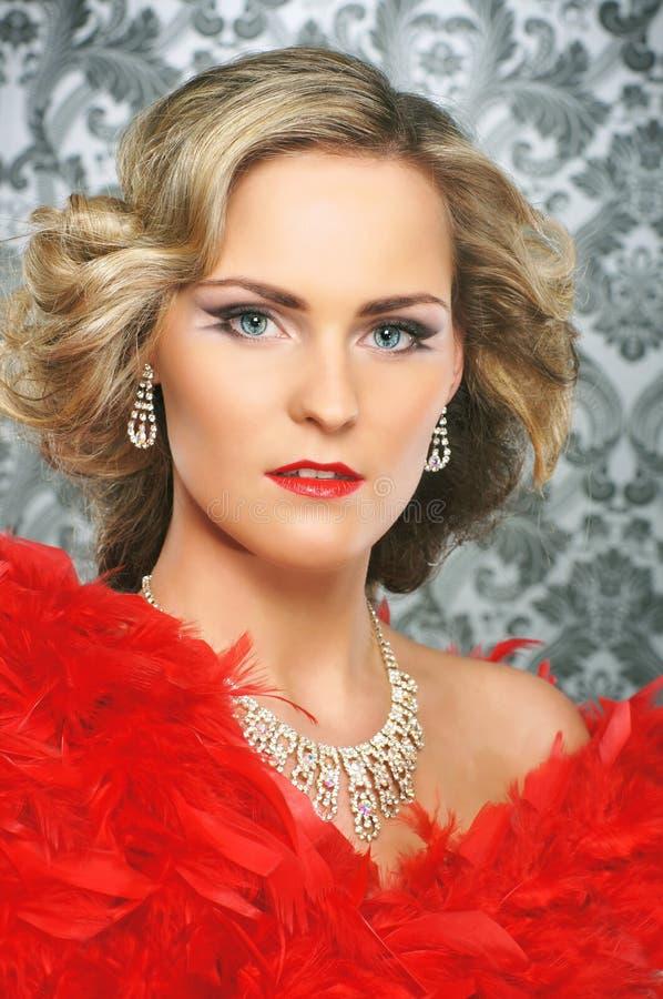 Retrato de una mujer rubia atractiva en plumas rojas imagen de archivo libre de regalías
