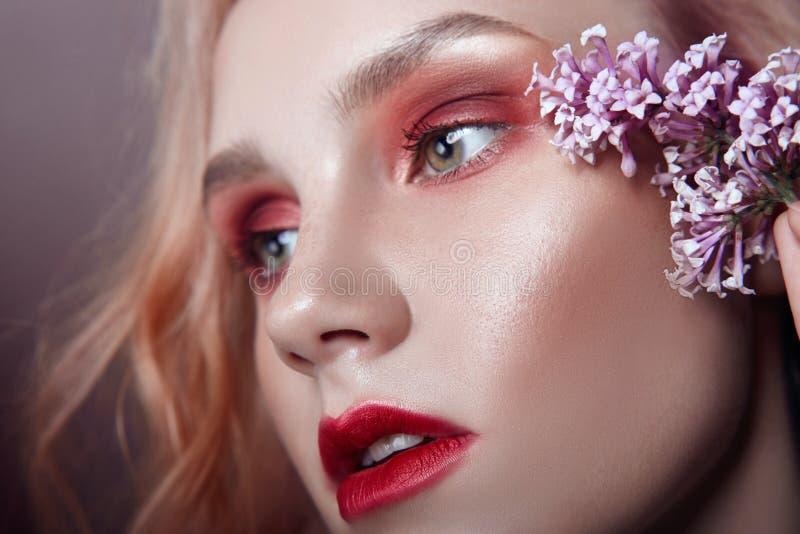 Retrato de una mujer rubia con los pétalos de la flor en su primer de la cara, maquillaje rojo brillante y lápiz labial Hidración imagen de archivo