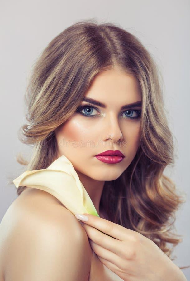 Retrato de una mujer rubia hermosa con un peinado con los rizos y el maquillaje hermoso, con la cala blanca en su mano imagenes de archivo
