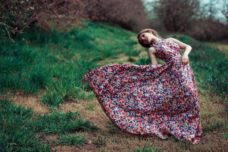 Retrato de una mujer rubia joven en un fondo de los árboles de la primavera Giro de la muchacha vestido rosado que agita en el vi imágenes de archivo libres de regalías