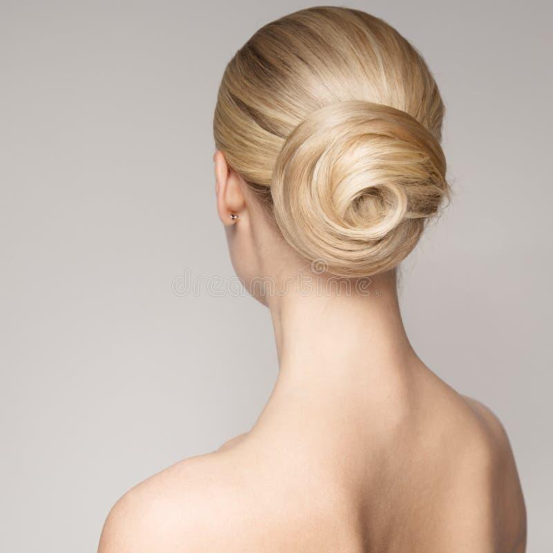 Retrato de una mujer rubia joven hermosa con el peinado del bollo fotografía de archivo