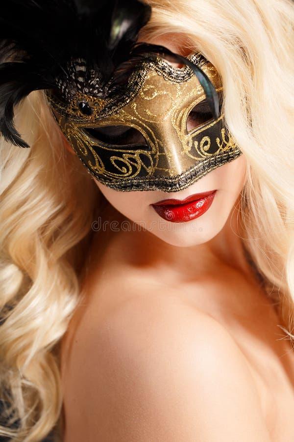 Retrato de una mujer rubia joven hermosa con la máscara de teatro en su cara en un fondo oscuro foto de archivo libre de regalías