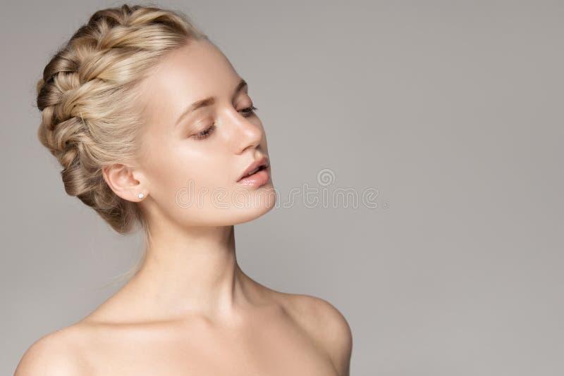 Retrato de una mujer rubia joven hermosa con los pelos de la corona de la trenza imagenes de archivo