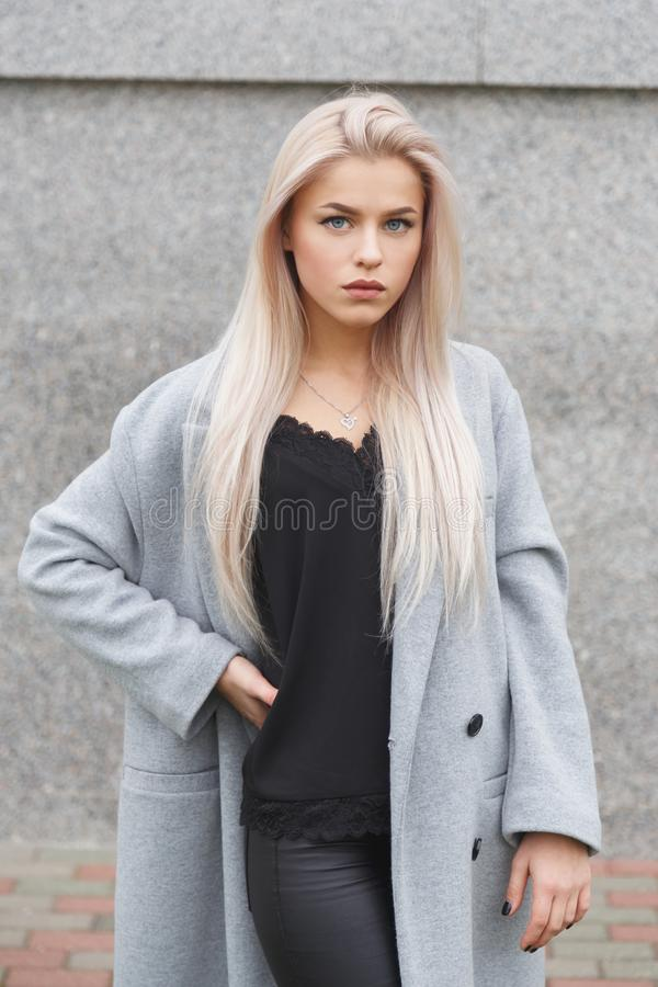 Retrato de una mujer rubia joven hermosa en capa gris y pantalones de cuero negros Mirada de la moda de la calle imagen de archivo