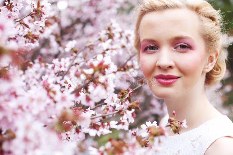 Retrato de una mujer rubia joven hermosa en un fondo de flores de cerezo rosadas en primavera foto de archivo