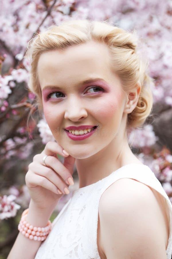Retrato de una mujer rubia joven hermosa en un fondo de flores de cerezo rosadas en primavera imagenes de archivo