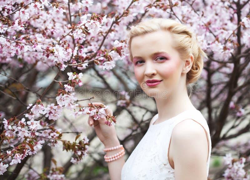 Retrato de una mujer rubia joven hermosa en un fondo de flores de cerezo rosadas en primavera foto de archivo libre de regalías