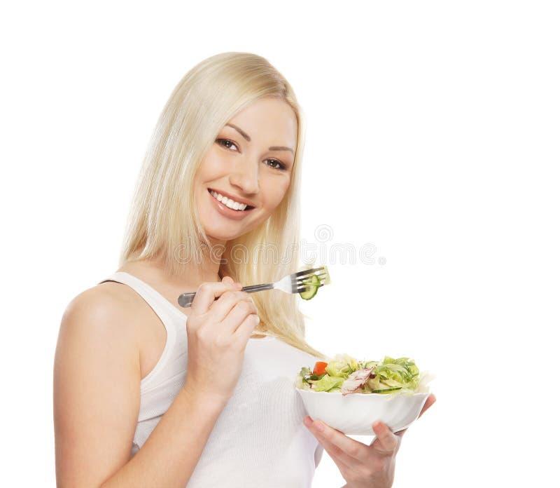 Retrato de una mujer rubia joven que come una ensalada imágenes de archivo libres de regalías
