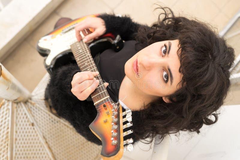 Retrato de una mujer seria mientras que juega en una guitarra eléctrica fotos de archivo