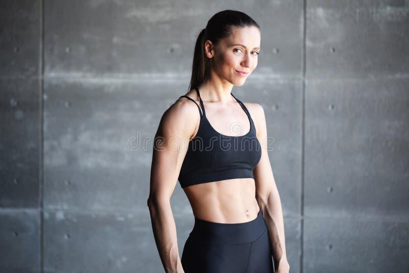 Retrato de una mujer sonriente en ropa deportiva negra foto de archivo