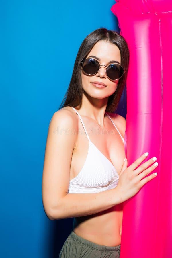 Retrato de una mujer sonriente joven emocionada vestida en el traje de baño blanco que presenta con el colchón inflable rosado ai imagenes de archivo