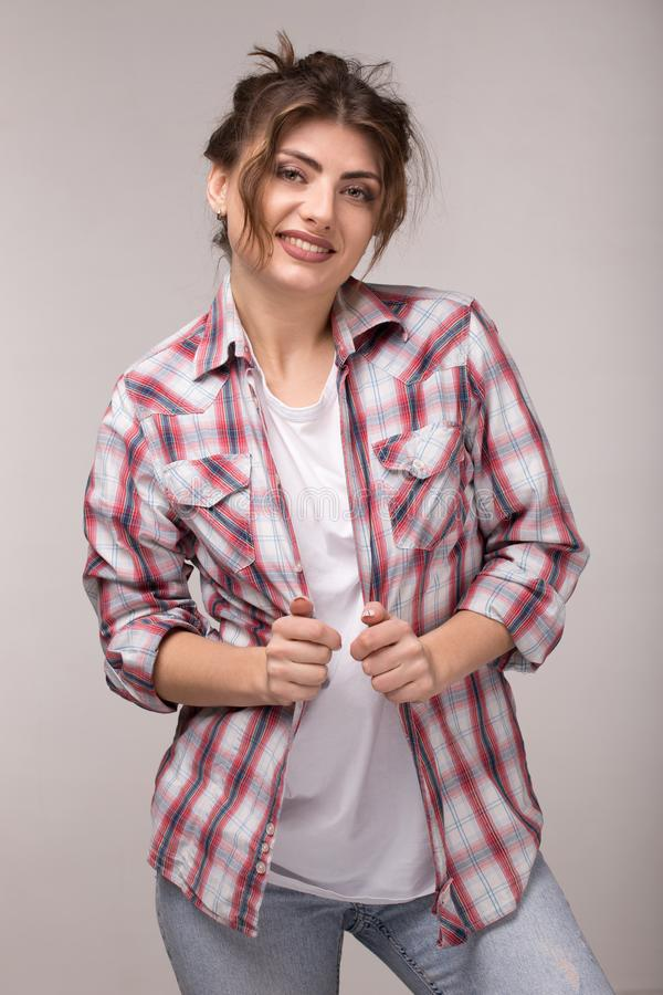 Retrato de una mujer sonriente joven en camisa de tela escocesa y la camiseta blanca, colocándose sobre la pared gris imagen de archivo