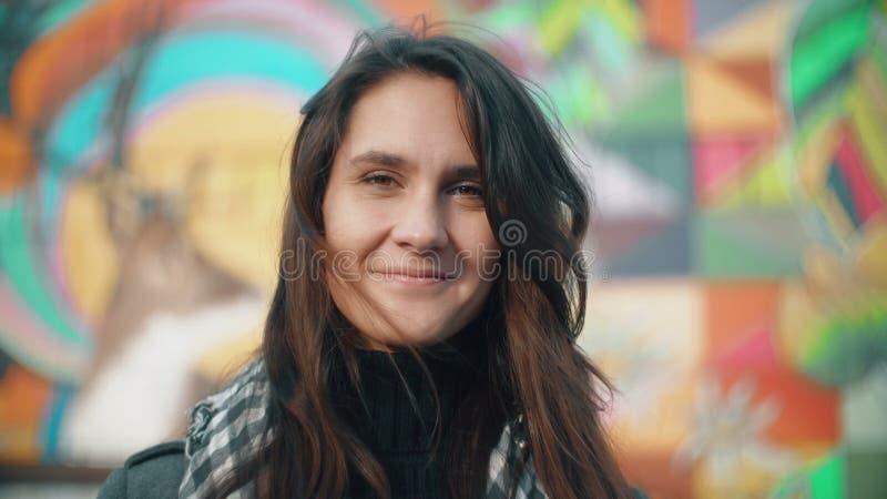 Retrato de una mujer sonriente joven en los rayos del sol poniente en un fondo colorido Primer 4K fotos de archivo libres de regalías