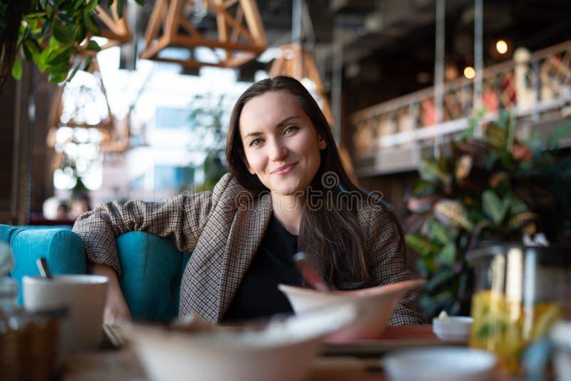 Retrato de una mujer sonriente joven en una tabla en un restaurante con un fondo borroso fotografía de archivo libre de regalías