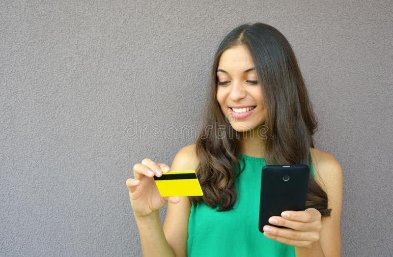 Retrato de una mujer sonriente joven que compra en línea con un smartphone al aire libre fotos de archivo