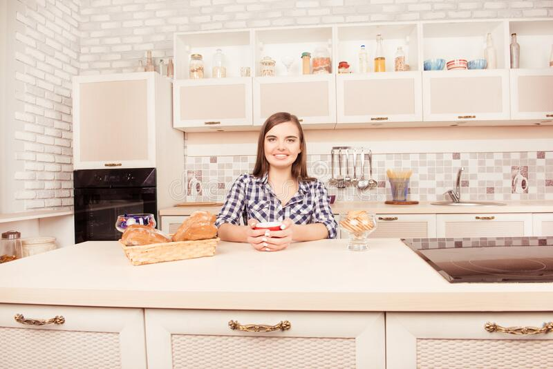 Retrato de una mujer sonriente tomando café con pasteles al horno imágenes de archivo libres de regalías
