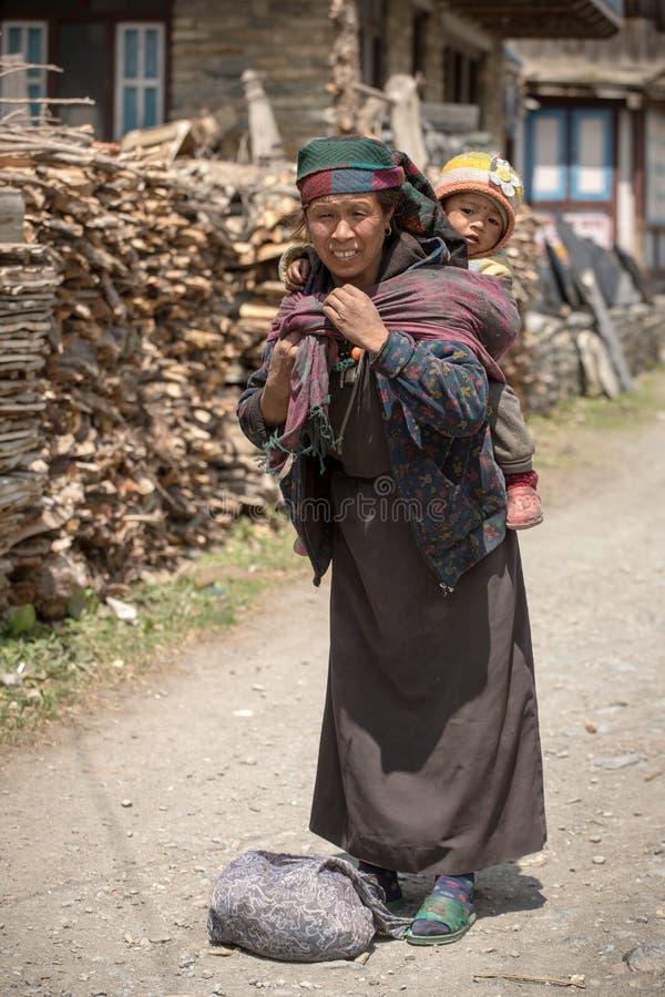 Retrato de una mujer tibetana no identificada con un bebé fotografía de archivo