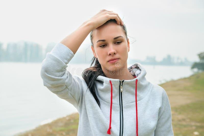 Retrato de una mujer triste joven con dolor de cabeza, cansancio o frío d fotos de archivo