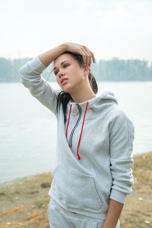 Retrato de una mujer triste joven con dolor de cabeza, cansancio o frío d imagen de archivo libre de regalías