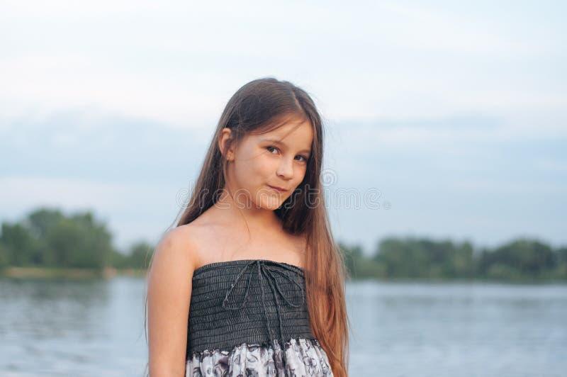 Retrato de una niña bronceada en sundress por el arena de mar foto de archivo