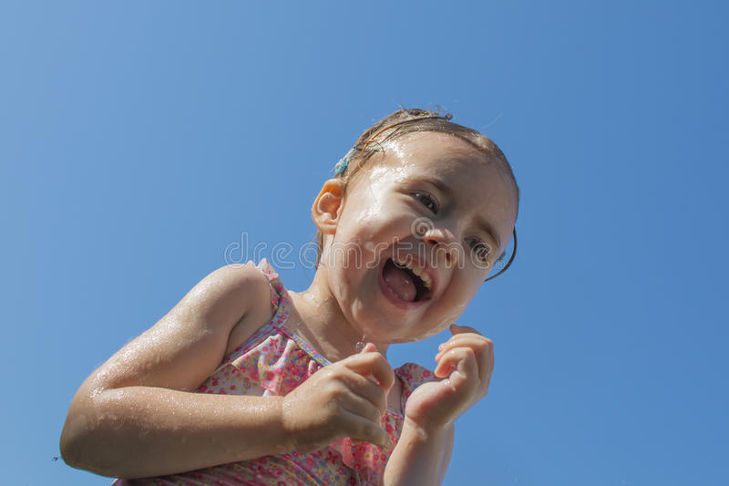 Retrato de una niña contra el cielo azul foto de archivo libre de regalías