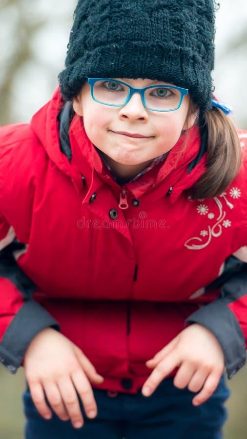 Retrato de una niña en un casquillo negro y lentes azules encendido fotografía de archivo