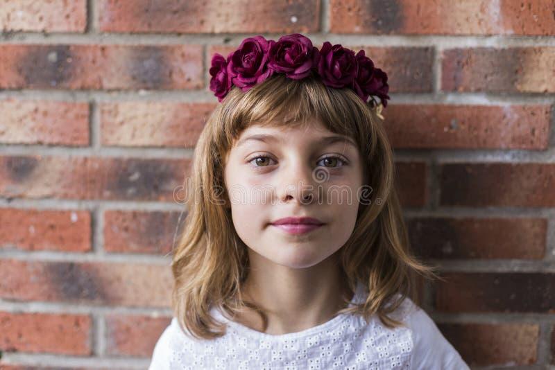 retrato de una niña hermosa con rosas rojas en la cabeza. Fondo del ladrillo. lifestyle fotografía de archivo libre de regalías