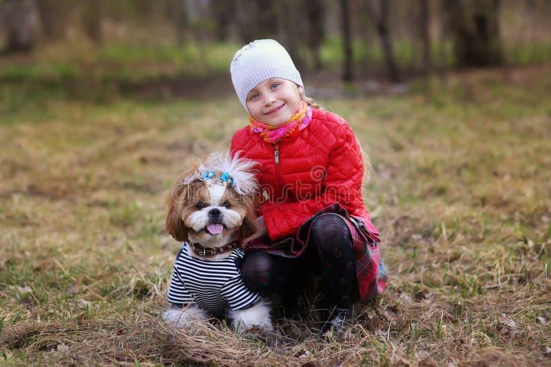 Retrato de una niña linda con su perro casero foto de archivo