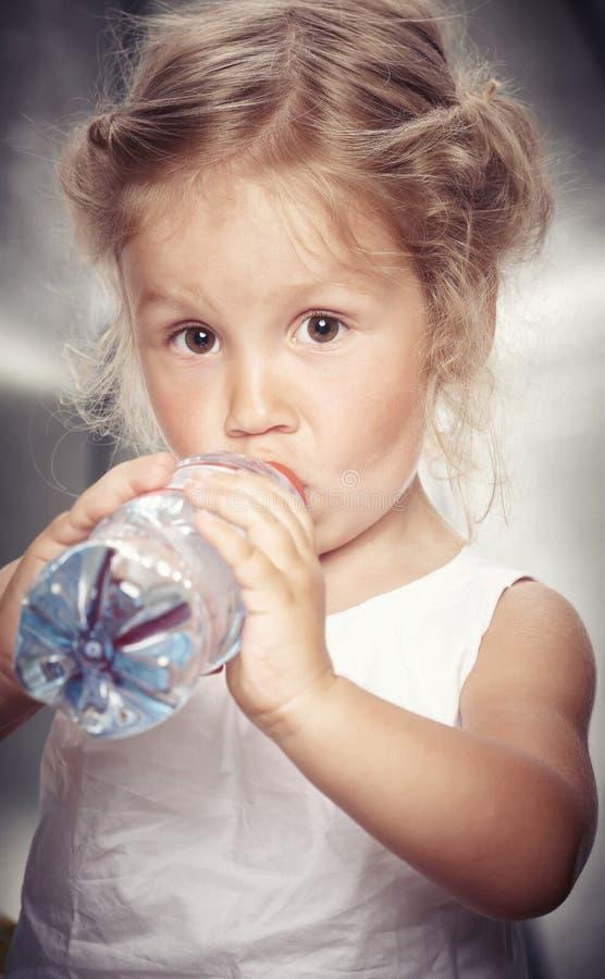 Retrato de una niña linda divertida en una ropa informal, agua de la bebida mientras que se sienta en estudio foto de archivo libre de regalías