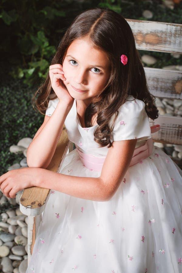 Retrato de una niña linda que se sienta en el jardín florecido imagenes de archivo