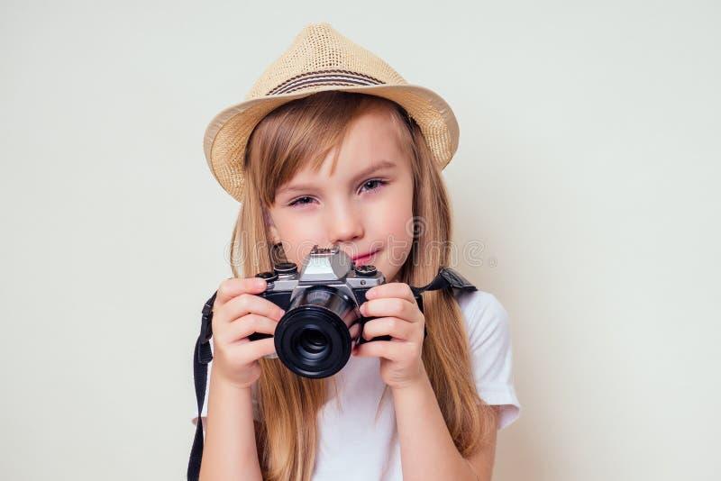 Retrato de una niña pequeña con una cámara. Imagen de una linda chica en un fotógrafo turístico de sombrero de paja fotos de archivo