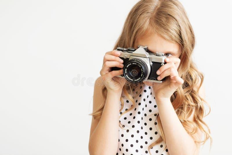 Retrato de una niña preciosa con la cámara vieja de la película de SLR imagen de archivo