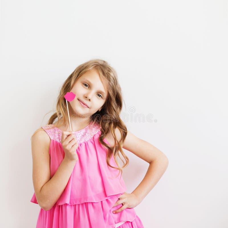 Retrato de una niña preciosa con los labios de papel rosados divertidos foto de archivo