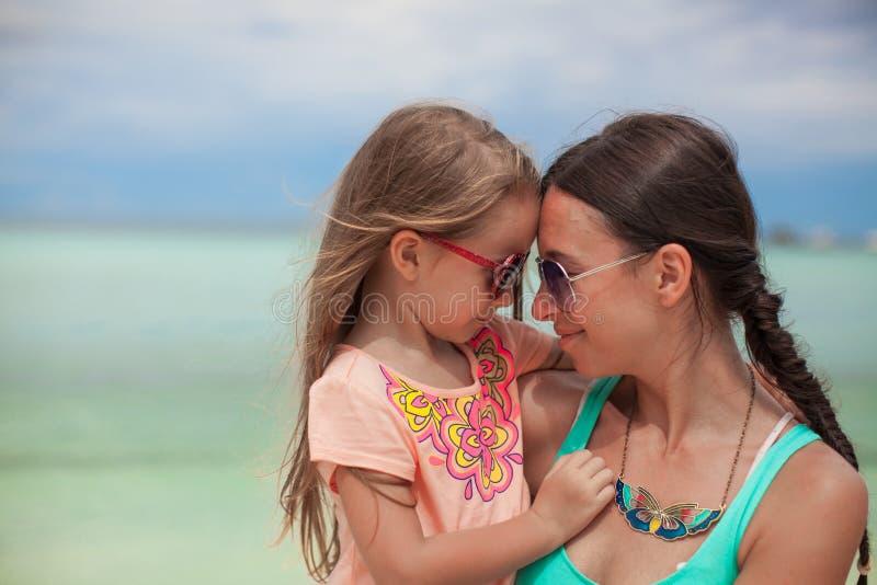 Retrato de una niña que abraza con su madre imagen de archivo