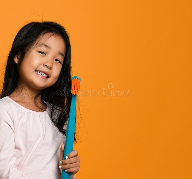 Retrato de una niña que sostiene un cepillo de dientes sobre fondo amarillo imágenes de archivo libres de regalías