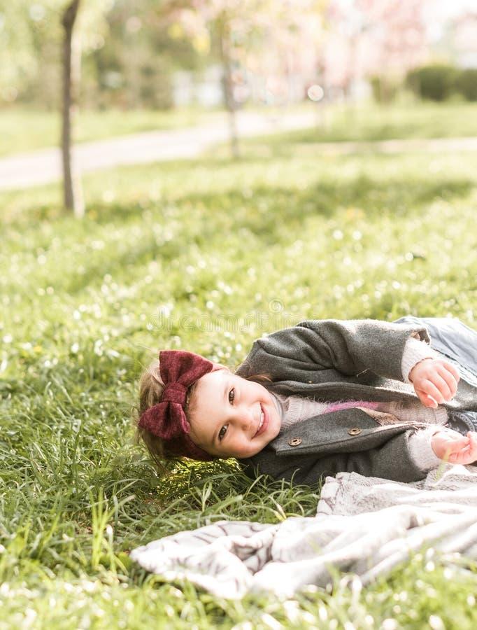 Retrato de una niña sonriente divertida en una tela escocesa en el parque fotos de archivo libres de regalías
