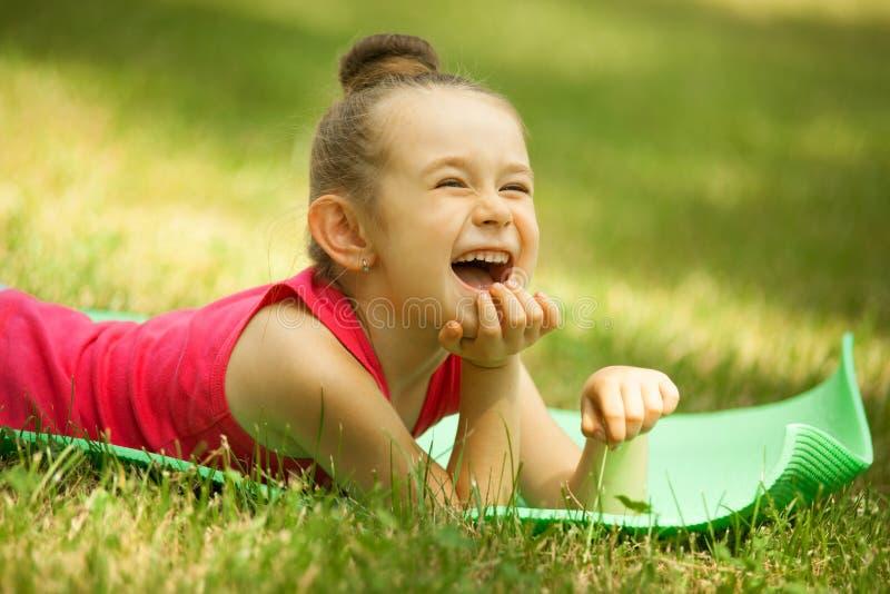 Retrato de una niña sonriente, mintiendo en verde imágenes de archivo libres de regalías