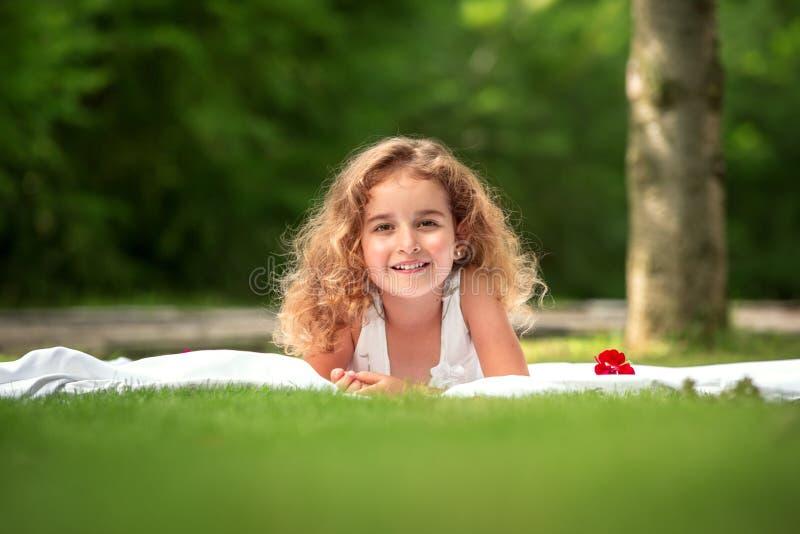 Retrato de una niña sonriente que miente en hierba verde imagenes de archivo
