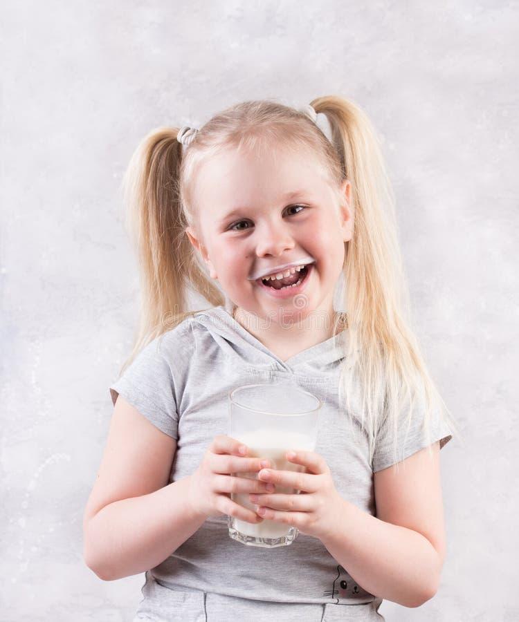 Retrato de una niñita sosteniendo una taza de leche, con fondo gris imágenes de archivo libres de regalías