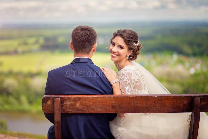 Retrato de una novia feliz que se sienta en un banco en el top de la colina con el novio y que mira detrás foto de archivo libre de regalías