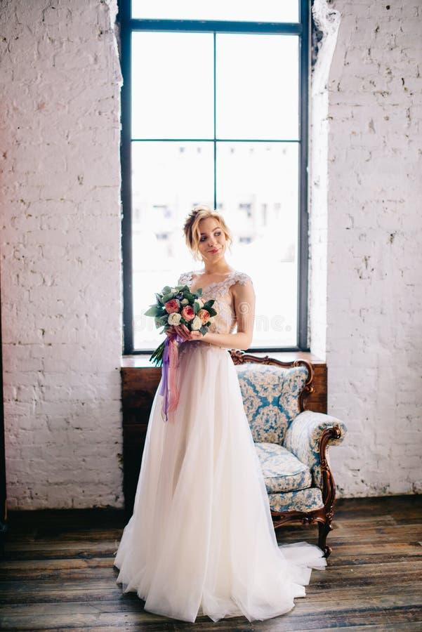 Retrato de una novia hermosa joven en un desván delante de una ventana imagenes de archivo