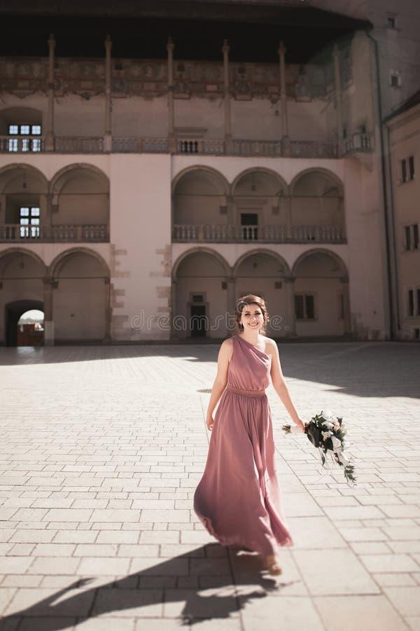 Retrato de una novia joven hermosa que se coloca entre las columnas cerca del edificio viejo y el ramo nupcial de la tenencia fotografía de archivo