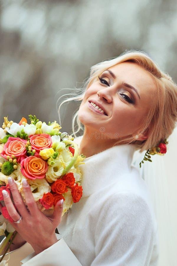 Retrato de una novia sonriente feliz, sosteniendo las flores y mirando a fotografía de archivo