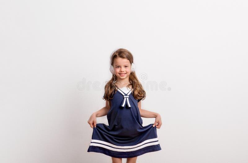 Retrato de una pequeña muchacha con los auriculares en estudio en un fondo blanco fotografía de archivo