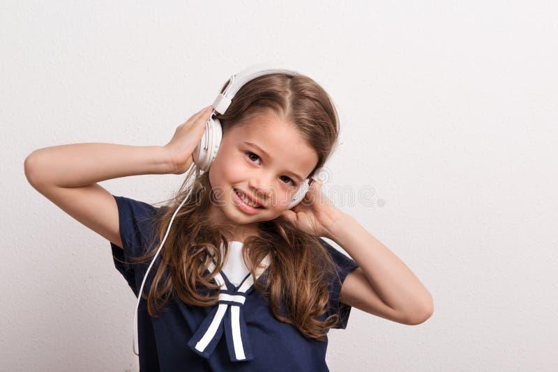 Retrato de una pequeña muchacha con los auriculares en un estudio imagen de archivo libre de regalías