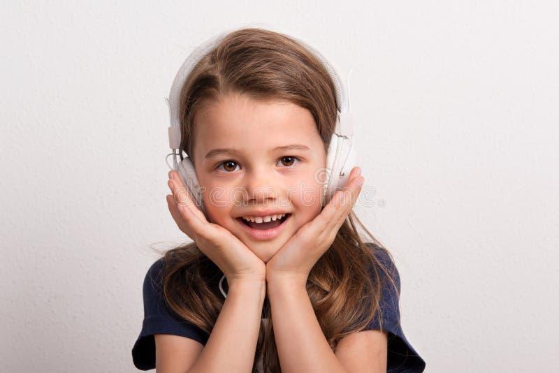 Retrato de una pequeña muchacha con los auriculares en un estudio imágenes de archivo libres de regalías