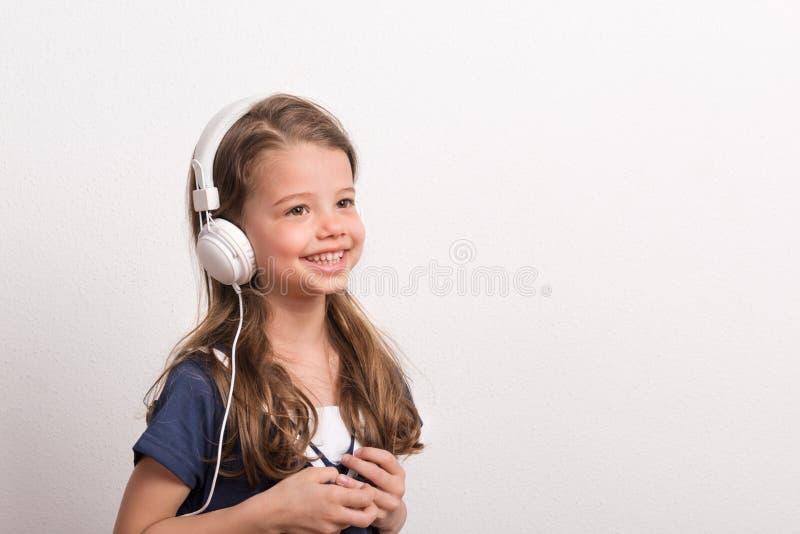 Retrato de una pequeña muchacha con los auriculares en un estudio Copie el espacio imagenes de archivo